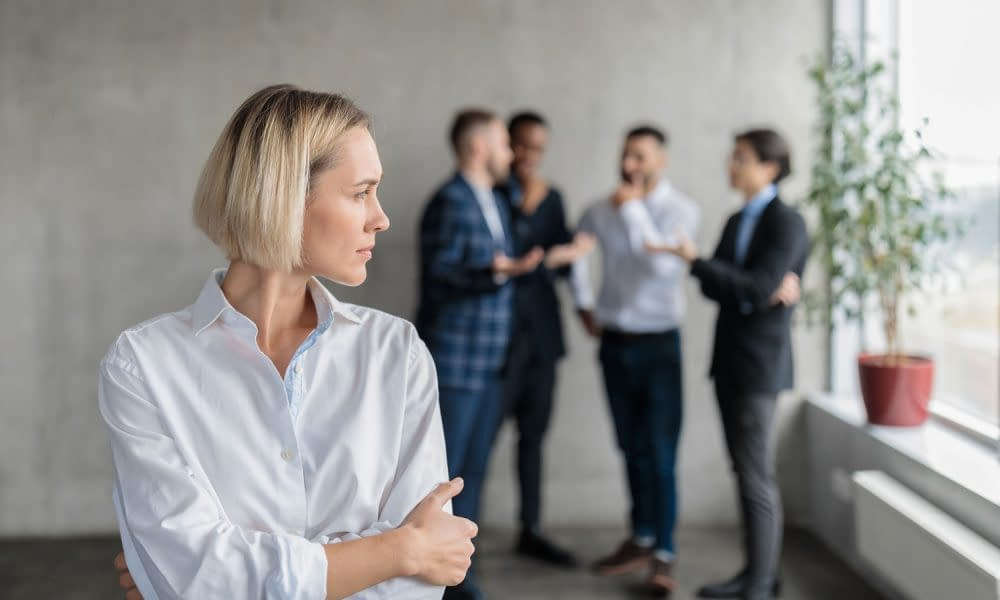 Male Coworkers Whispering Behind Back Of Unhappy Businesswoman I
